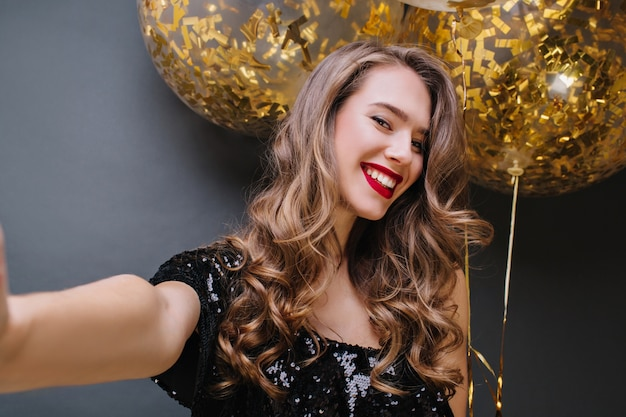 Selfie portret van jonge charmante vrouw met rode lippen, lang donkerbruin haar lachend met grote ballonnen vol met gouden tinsels. positiviteit uiten, feest vieren.