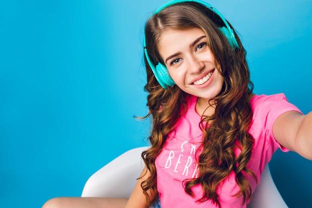 Selfie-portret van mooi meisje met lang krullend haar koelen op blauwe achtergrond in de studio. ze luistert naar muziek en lacht naar de camera.