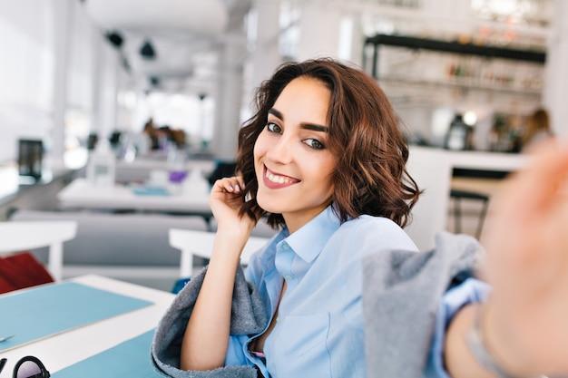 Selfie-portret van schattige brunette meisje met kort haar zittend aan tafel in grijze plaid op terras in restaurant. ze draagt een blauw shirt en ziet er vrolijk uit.