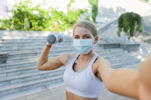 Selfie portret van sportvrouw in sportkleding en medisch beschermend gezichtsmasker met halters buitenshuis. fitnesslessen tijdens covid-19
