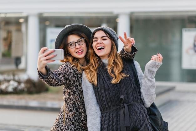 Selfie portret van vrolijke modieuze vrouwen met plezier op zonnige straat in de stad. stijlvolle look, plezier hebben, reizen met vrienden, glimlachen, echte positieve emoties uitdrukken.