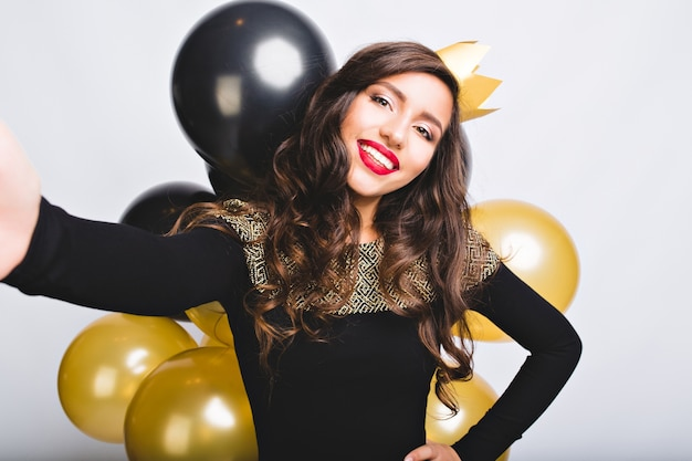 Selfie portret vrolijke vrouw met lang donkerbruin krullend haar, gele kroon, luxe zwarte jurk. nieuwjaar vieren, verjaardagsfeestje, plezier maken met gouden en zwarte ballonnen.