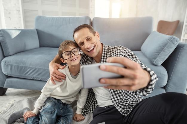 Selfie tijd. aantrekkelijke, vrolijke, blonde jongen die lacht en een grote bril draagt en zijn vader die selfies van hen neemt