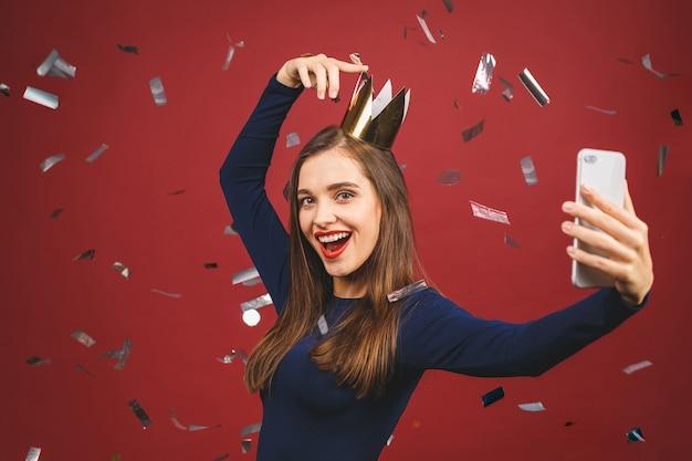 Selfie tijd! portret met copyspace lege plaats van vertrouwen trotse arrogante jonge vrouw met gouden kroon op haar hoofd geïsoleerd op rode achtergrond.