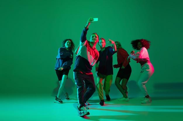 Selfie tijd. stijlvolle mannen en vrouwen die hiphop dansen in lichte kleding op een groene achtergrond in de danszaal in neonlicht. jeugdcultuur, beweging, stijl en mode, actie. modieus portret.