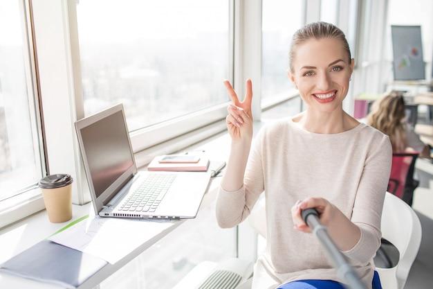 Selfie van een glimlachende vrouw die aan de tafel zit