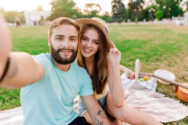 Selfie van een jong koppel op de picknick in het park met fruitmand