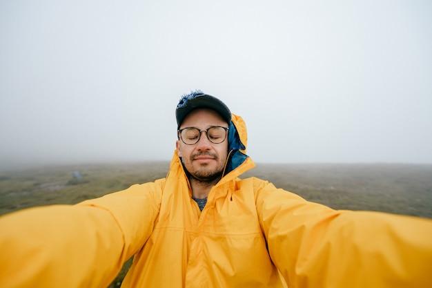 Selfie van een man met ogen gesloten in gele regenjas op verlaten plek met wolken en mist op de achtergrond.