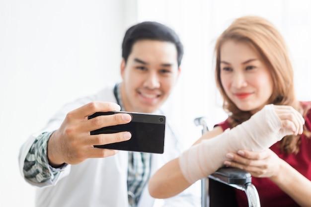 Selfie van glimlachende man arts met een vrouwelijke patiënt draag arm splint voor betere genezing zitten in een rolstoel abstract vervagen met focus met behulp van een smartphone in het ziekenhuis van de kamer.
