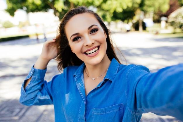 Selfie van grappig aantrekkelijk meisje dat neemt selfie op straat
