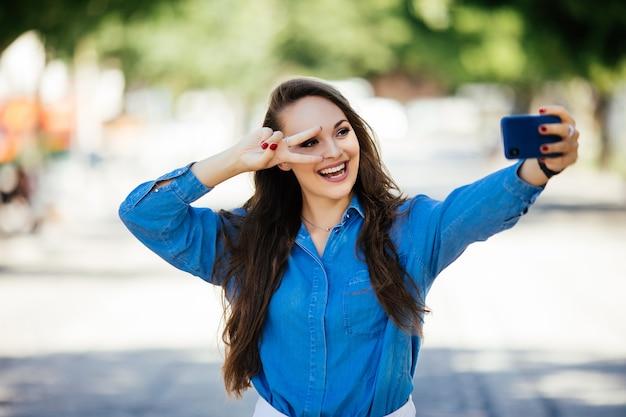 Selfie van grappig aantrekkelijk meisje steenbolk en v-sign op straat tonen