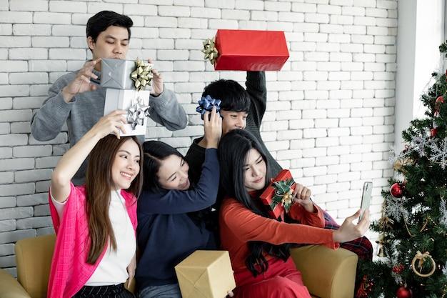 Selfie van groep jonge aziatische met geschenken thuis in het vieren van kerstfestival. thaise tieners vieren kerstmis en nieuwjaar. prettige kerstdagen en fijne feestdagen.