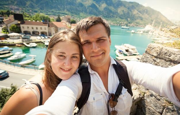 Selfie van jonge gelukkige paar poseren tegen zee baai op zonnige dag
