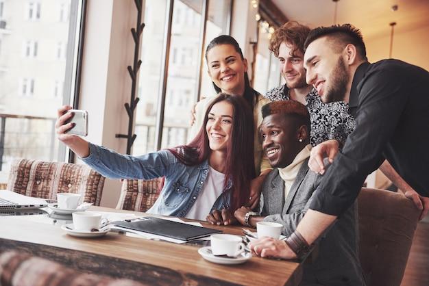 Selfie van jonge lachende mensen plezier samen. beste vrienden nemen selfie buitenshuis met achtergrondverlichting. gelukkig vriendschapsconcept