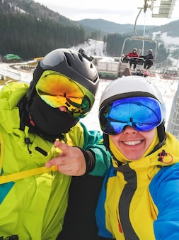 Selfie van paar in skiresort gelukkig lachende vrouw in bril
