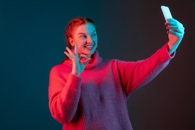 Selfie, vlog, videogesprek maken. het portret van de blanke vrouw geïsoleerd op de achtergrond van de gradiëntstudio in neonlicht. mooi vrouwelijk model met rood haar. concept van menselijke emoties, gezichtsuitdrukking, advertentie.