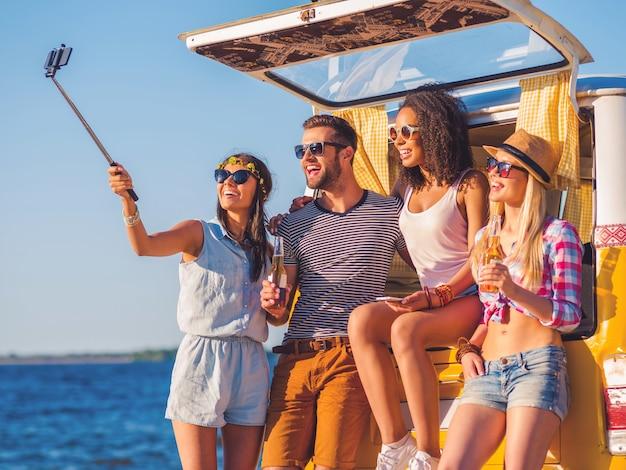Selfie voor een roadtrip. groep gelukkige jonge mensen leunend op de kofferbak van hun retro minivan en selfie maken met zee of rivier op de achtergrond