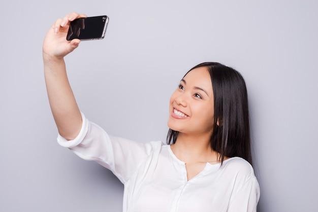 Selfie! vrolijke jonge aziatische vrouw die mobiele telefoon vasthoudt en selfie maakt met haar smartphone terwijl ze tegen een grijze achtergrond staat
