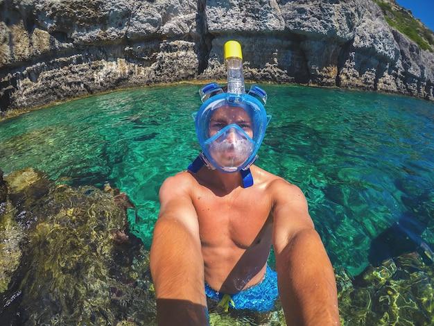 Selfiefoto van een jonge, gezonde, gespierde man met een snorkelmasker die tijdens de zomervakantie in de turquoise exotische zee bij de rotsen staat.