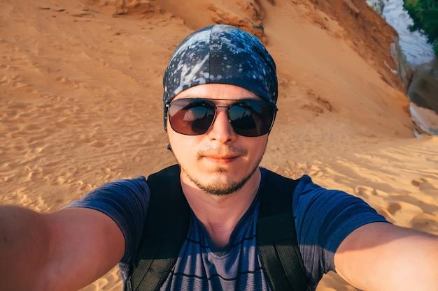 Selfiemannen in een bandana op de achtergrond van zand