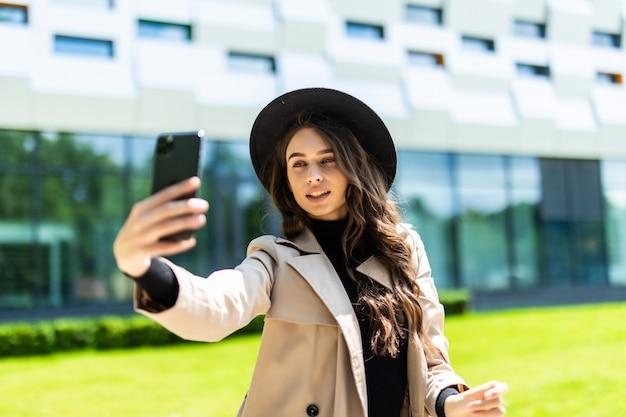 Selfieportret van een jonge stijlvolle toeristenvrouw gekleed in een jas en hoed op een van europese stedelijke architectuur