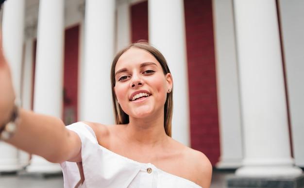 Selfieportret van een vrolijke charismatische vrouw tegen een gebouw met zuilen in de buitenlucht