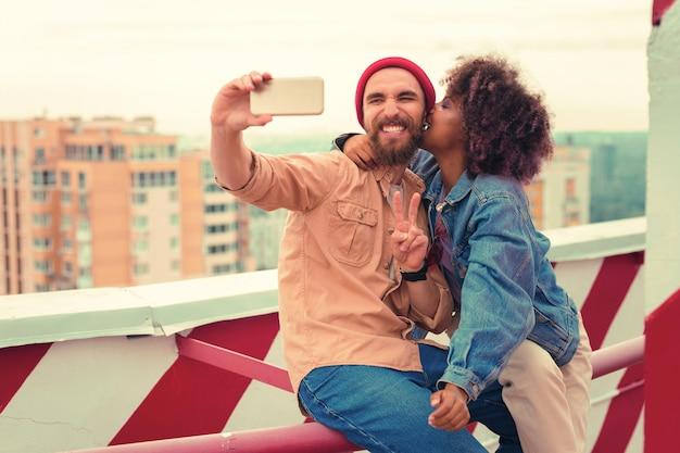 Selfies nemen. positieve bebaarde jonge man glimlachend en fotograferen terwijl zijn mooie vriendin hem kuste