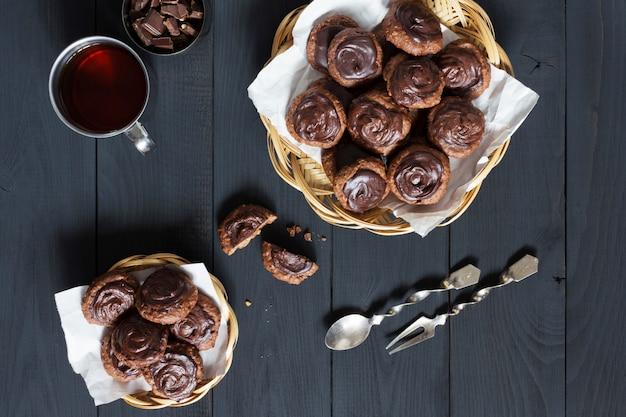 Selfmade chocoladekoekjes met thee op een donkere lijst