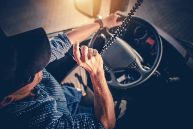 Semi vrachtwagenchauffeur in gesprek met andere vrachtwagenchauffeurs via cb-radio.