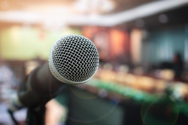 Seminar conferentie concept: close-up microfoons op abstract wazig van spraak in vergaderruimte, voorkant sprekende vervagen mensen in evenementenhal met lens lichte flare in hotel achtergrond