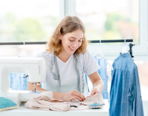Sempstress schetst schets van toekomstig kledingstuk