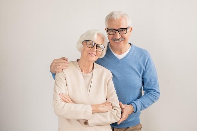 Senior aanhankelijk koppel in slimme vrijetijdskleding die naar je kijkt terwijl je staat