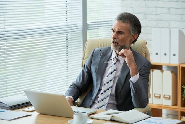 Senior advocaat die nadenkt over de uitdagende rechtszaak in zijn kantoor bijtend brillentempel
