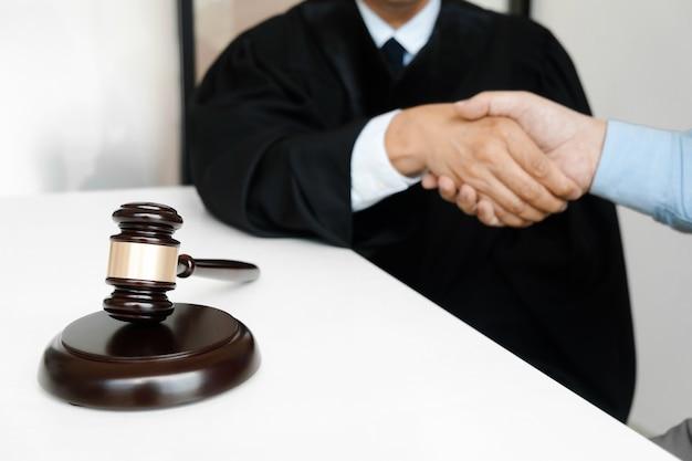 Senior advocaat overleg met rechtvaardigheid hamer handen schudden met klant