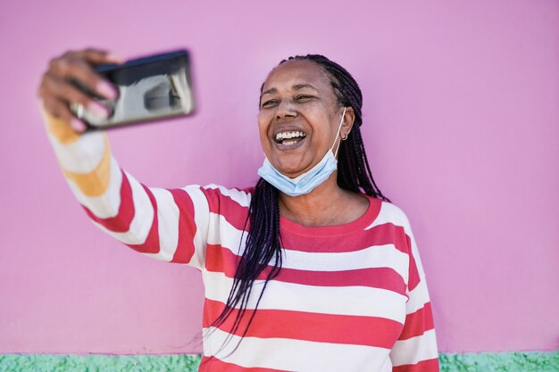 Senior afrikaanse vrouw die tijdens een videogesprek met smartphone in de stad praat terwijl ze een veiligheidsmasker onder de kin draagt - oudere zwarte vrouw die mobiele telefoon gebruikt om een selfie te maken
