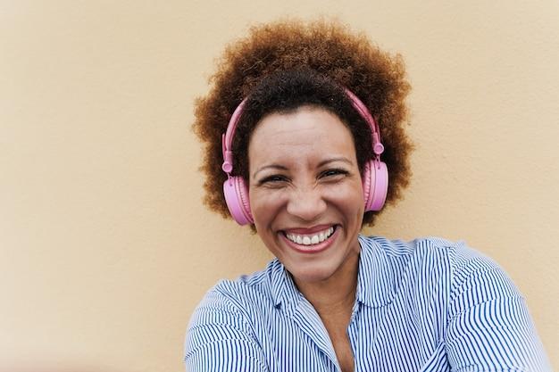 Senior afrikaanse vrouw luisteren muziek met koptelefoon - focus op gezicht