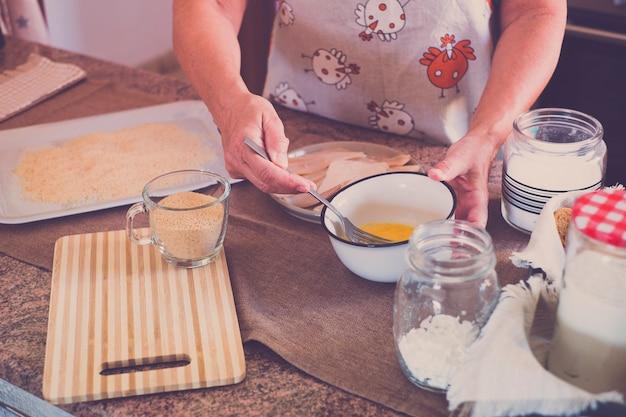 Senior alleen thuis vis koken in de keuken - zeer gefocust binnen - volwassen en blanke 60s vrouw - gepensioneerde vrouw
