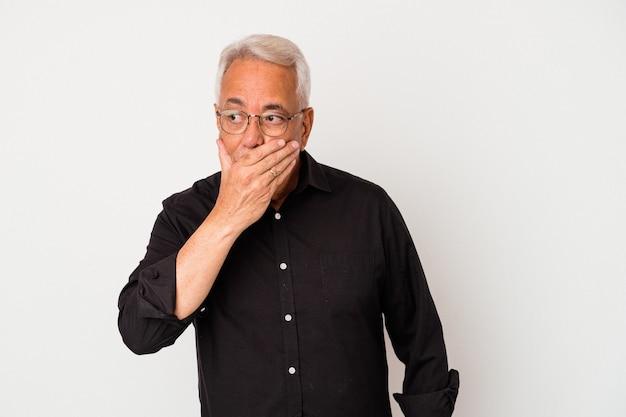 Senior amerikaanse man geïsoleerd op een witte achtergrond die betrekking hebben op de mond met handen op zoek bezorgd.