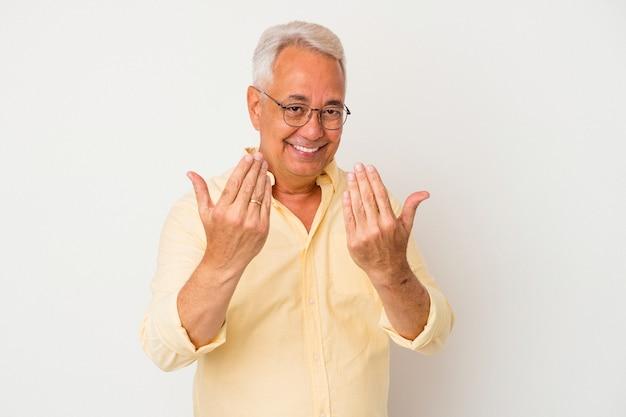Senior amerikaanse man geïsoleerd op een witte achtergrond die met de vinger naar je wijst alsof uitnodigend dichterbij komt.