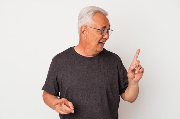 Senior amerikaanse man geïsoleerd op een witte achtergrond die naar verschillende kopieerruimten wijst, een van hen kiest, toont met de vinger.