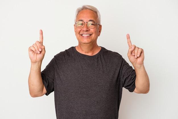 Senior amerikaanse man geïsoleerd op een witte achtergrond geeft aan dat met beide voorvingers omhoog een lege ruimte wordt weergegeven.