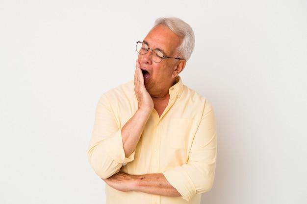 Senior amerikaanse man geïsoleerd op een witte achtergrond geeuwen met een vermoeid gebaar voor mond met de hand.