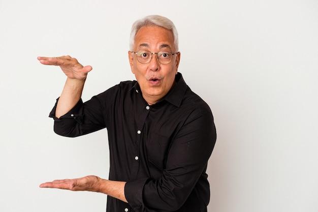 Senior amerikaanse man geïsoleerd op een witte achtergrond geschokt en verbaasd met een kopie ruimte tussen handen.
