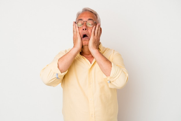 Senior amerikaanse man geïsoleerd op een witte achtergrond jammerend en huilend troosteloos.