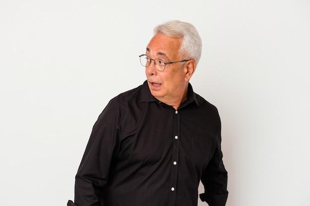 Senior amerikaanse man geïsoleerd op een witte achtergrond kijkt opzij glimlachend, vrolijk en aangenaam.