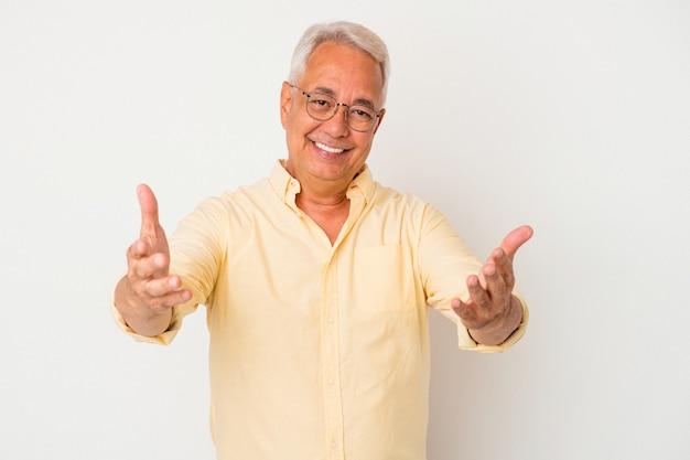 Senior amerikaanse man geïsoleerd op een witte achtergrond met een welkome uitdrukking.
