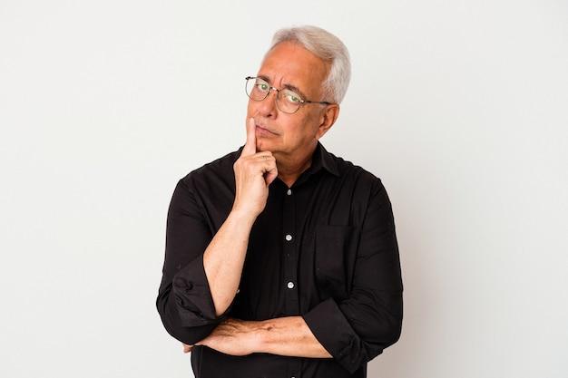 Senior amerikaanse man geïsoleerd op een witte achtergrond op zoek zijwaarts met twijfelachtige en sceptische uitdrukking.