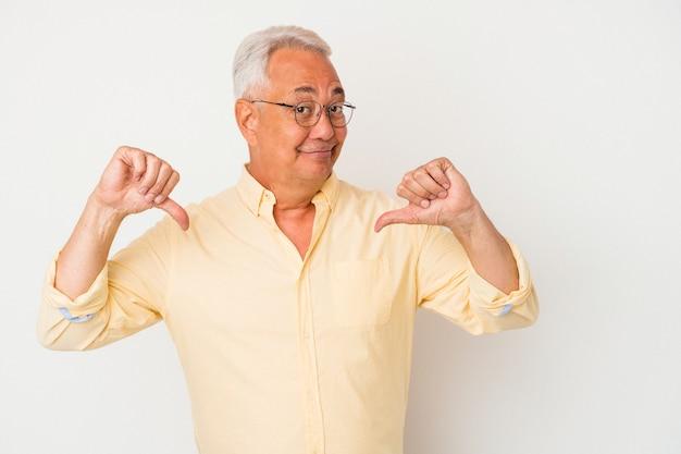 Senior amerikaanse man geïsoleerd op een witte achtergrond voelt zich trots en zelfverzekerd, voorbeeld om te volgen.