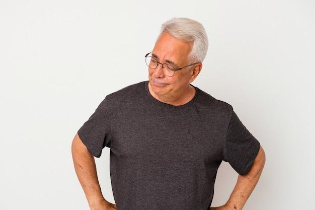 Senior amerikaanse man geïsoleerd op witte achtergrond haalt zijn schouders op en verwarde ogen.