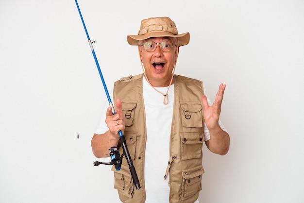 Senior amerikaanse visser bedrijf staaf geïsoleerd op een witte achtergrond verrast en geschokt. Premium Foto